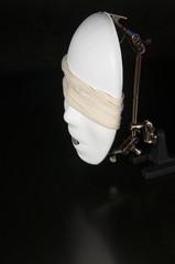 Iron alligator clip stand with white bandaged mask on a black background
