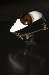 Iron alligator clip stand with white mask wearing sunglasses on a black background