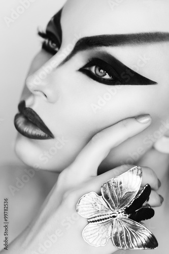 Black and white portrait of beautiful model with fantasy creative art makeup white background