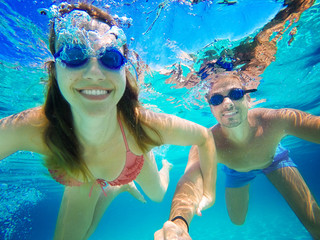 Couple in love refreshing underwater on vacation. Diving. Wide angle selfie shot.