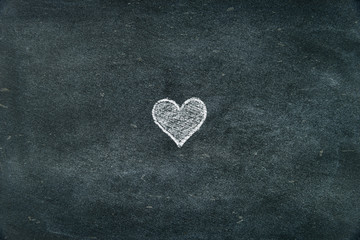 Hand drawing heart shape symbol on blackboard