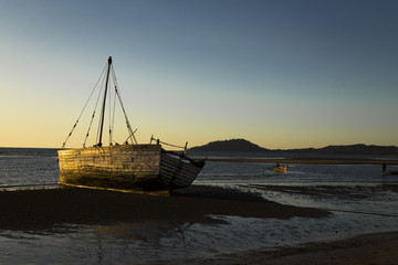 Old white vessel stranded on low tide Madagascar sunset