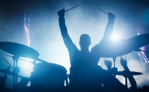 Drummer playing on drums on music concert. Club lights