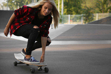 Young woman with skating board on the road