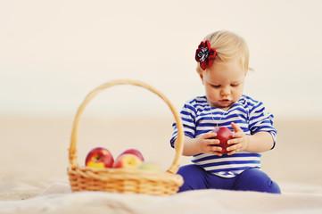 Маленькая девочка играет с яблоками  на пляже