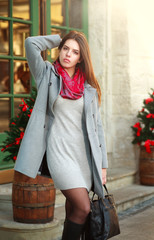 Attractive fashion girl in coat on the city street