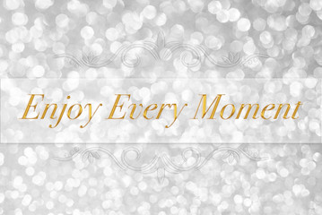 Enjoy every moment quote typography on white glitter bokeh abstr