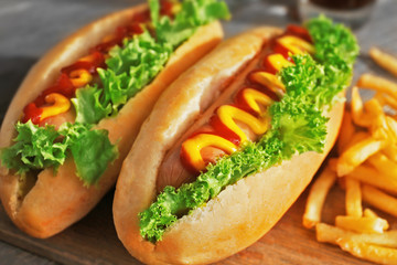 Delicious hot-dogs with French fries on wooden chopping board, close up
