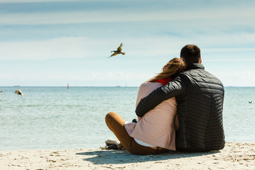 couple sitting on beach rear view