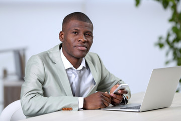 Handsome businessman with laptop in his office, close up