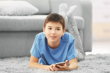 Boy lying with mobile phone on a carpet at home