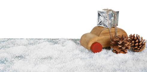 Wooden toy car with gift box and cones on a snowy table over white background