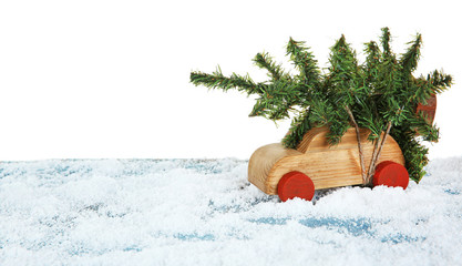 Wooden toy car with Christmas tree on a snowy table over white background