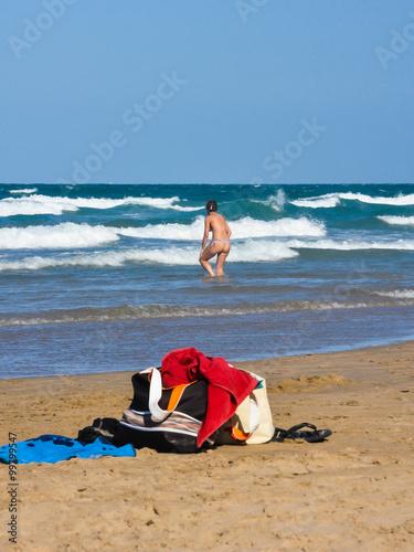 objetos de playa y mujer bañándose playa de gandia valencia