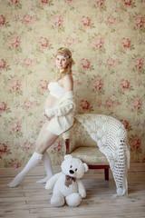красивая беременная блондинка в светлой комнате. Счастлива