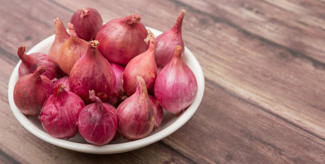 Shallots in white bowl over wooden background