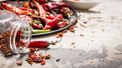 Dried red Chili peppers on a tray and in the jar.