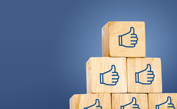 Thumb up icon on wood cube at dark blue background, leave space