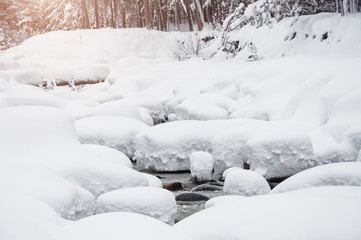 Snowfall on the river in winter forest