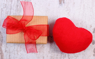 Wrapped gift for Valentines day and red heart on old wooden table