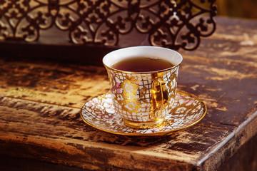 Closeup image of vintage porcelain tea cup on  golden saucer