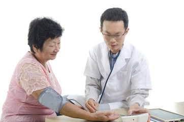 Image of a doctor and his nurse checking up a senior patient in