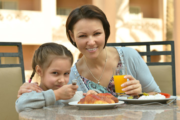 girl with mother eating in cafe