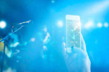 Music fans takes a photo of guitarist on stage in concert by smartphone