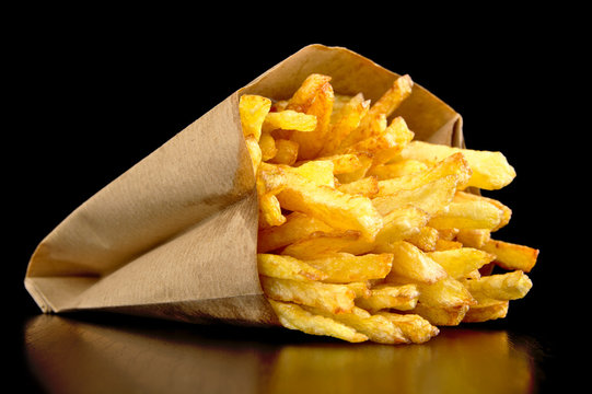 French fries in the paper bag isolated on black