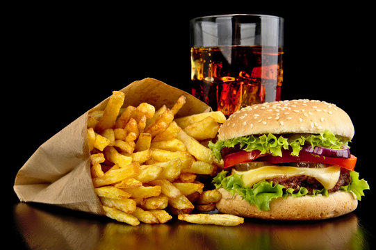 Big cheeseburger with glass of cola and french fries on black desk