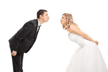 Young bride and groom going in for a kiss