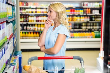 Beautiful woman with cart choosing product