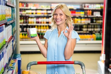 Smiling woman holding product and showing ok