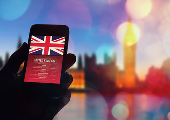 Hand holding smartphone with London city background.