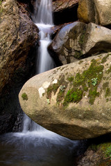 great wonders of nature - river waterfall surrounded by big rocks in long exposure