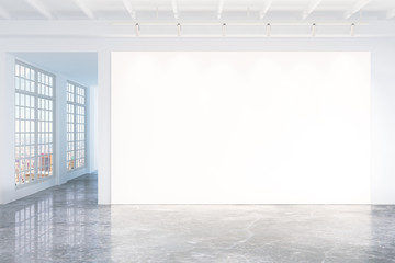 Blank white poster on white wall in empty loft room with concret