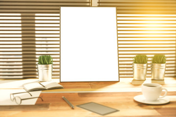 Blank picture frame on a wooden desk at sunset