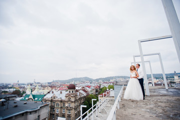 Elegant wedding couple on the roof with high-tech architecture l