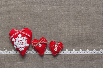 three red hearts and lace on burlap background