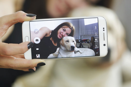 Girl photographing selfie with dog labrador at home