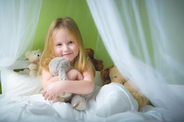Little girl sleep in bed with teddy bear