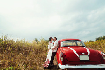 stylish bride and happy groom near red retro car on the backgrou