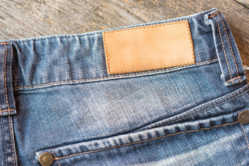 Blank leather label blue jeans on wooden background.