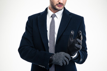 Modern attractive businessman in classic suit wearing fashionable gloves