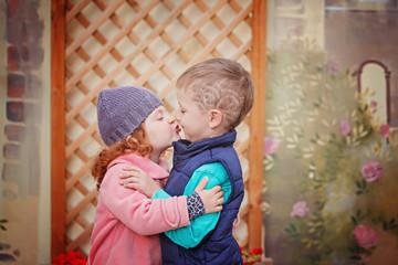 Little boy kissing smiling little girl on her cheek, outdoor por