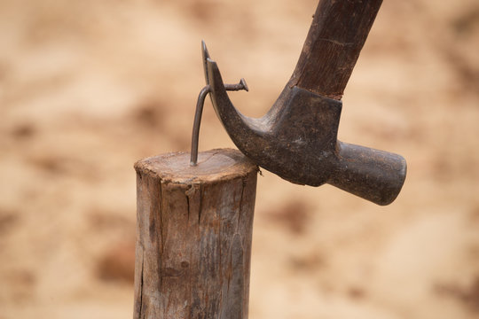 hammer pulling a nail out of wood