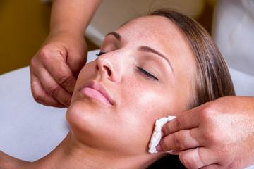 Fototapeta Freckles woman having a cosmetic treatment at the beauty salon. obraz