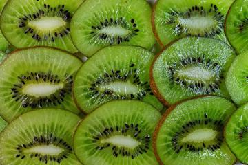 green background of sliced kiwi closeup