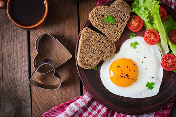 Printed roller blinds Egg Breakfast on Valentine's Day - fried eggs and bread in the shape of a heart and fresh vegetables. Top view