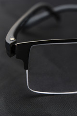 Part glasses with detail on the dust on the glass and hinge on a dark background